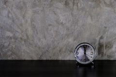 Dark wood table with alarm clock on gray concrete loft style wall royalty free stock photography