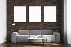 Dark wood walls living room, front. Front view of a living room with dark wooden walls, a long sofa and three framed vertical posters hanging above it. 3d Royalty Free Stock Photos