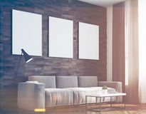 Dark wood walls living room, side, toned. Side view of a living room with dark wooden walls, a long sofa and three framed vertical posters hanging above it. 3d Royalty Free Stock Image