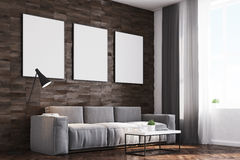 Dark wood walls living room, side. Side view of a living room with dark wooden walls, a long sofa and three framed vertical posters hanging above it. 3d Stock Photography