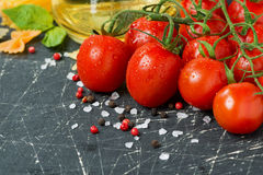 Dark wooden background with cherry tomatoes and ingredients Royalty Free Stock Photos