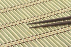 Dark wooden chopsticks on bamboo mat Stock Photo