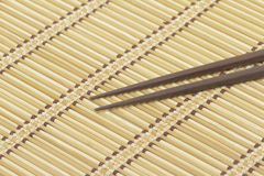 Dark wooden chopsticks on bamboo mat Royalty Free Stock Photography
