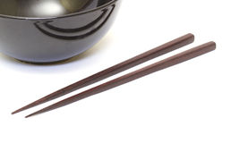 Dark wooden chopsticks and ceramic bowl Stock Photography