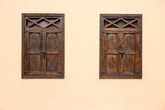 Dark wooden closed windows contrasting to light cream wall royalty free stock photo