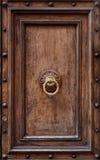 Dark wooden door panel with door knocker. Royalty Free Stock Image
