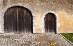 Dark wooden doors in old stone wall Royalty Free Stock Photos