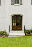 Dark wooden front door with a small arch and black rails with green grass Stock Image