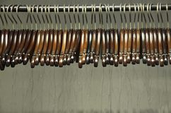 Dark wooden hangers on a rack. Side view of dark wooden hangers with copper colored hooks on a metal rack Royalty Free Stock Photo