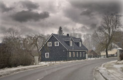 Dark wooden house by the road Royalty Free Stock Photography