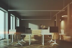 Dark and wooden office interior toned. Dark wall office interior with wooden computer tables and large windows. Blank displays. 3d rendering mock up toned image Stock Images