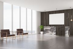 Dark wooden reception, armchairs and poster Stock Image