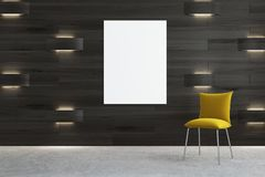 Dark wooden room with a yellow chair and a poster. Empty room interior with a yellow chair standing on a concrete floor. A poster on a black wooden wall with Royalty Free Stock Image