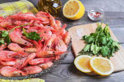 On a dark wooden table dish with shrimps raw Royalty Free Stock Image