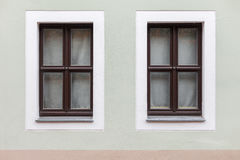 Dark wooden windows on a single wall. View of the front pistachio wall with two dark wood windows Royalty Free Stock Photo