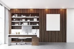 Dark wooden workplace with table. Dark wooden workplace with a table, a desktop standing on it and a bookcase behind it. Poster on the wall. 3d rendering. Mock Royalty Free Stock Photography