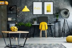 Dark workspace with wooden table. Citrus in basket on wooden table on black and white carpet in dark workspace with lamp Royalty Free Stock Photos
