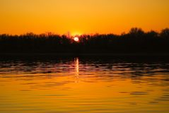Dark yellow sunset over the river. Dark orange sunset over the river. Beautiful evening landscape on the Volga river in the spring Royalty Free Stock Photos