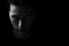 Dark young adult man portrait fade in black. Background Royalty Free Stock Photos
