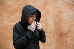 Dark young woman sad standing and smoking near urban wall portra Stock Photos