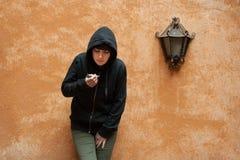 Dark young woman sad standing and smoking near urban wall portra Royalty Free Stock Photo