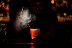 Darkened shot of bartender pours an alcohol cocktail using sprayer royalty free stock photography