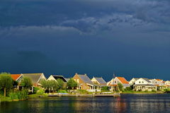 Darkened sky at lakeside holiday resort by sunset. Dramatic sky by a storm brewing over Dutch holiday homes at a lake by sunset Stock Photos