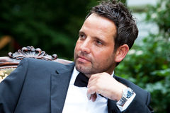 Handsome groom. Darkhaired handsome groom with bow tie is waiting for his bride and looking around Stock Photo