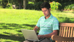 Darkhaired man using laptop outdoors Royalty Free Stock Photos