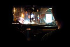 Darkly lit inside of a taxi drive in eastern Europe. Over the shoulder photo of a darkly lit taxi drive in eastern Europe. Taken on the street of Georgia`s Royalty Free Stock Image