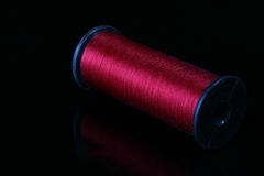 Darkly red threads. On the coil for industrial use. Threads are placed on a black reflecting background Royalty Free Stock Image