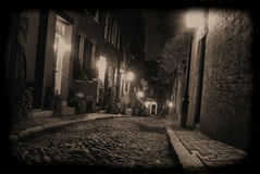 Darkness on the edge of town. Sepia toned image of an old 19th Century cobble stone road in Boston Massachusetts, lit only by the gas lamps revealing the royalty free stock photos