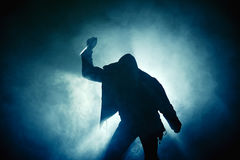 Darkness knife hand fog man. Fist and knife of a man in leather jacket and hoodie in fog in the backlight royalty free stock photography