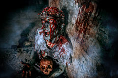 Darkness man. Bloodthirsty zombie chewing the skull of his victim. Halloween concept Stock Photos
