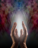 From the Darkness to the Light. Parallel male hands reaching up into a beam of white light on a black background with an ethereal misty energy descending royalty free stock images