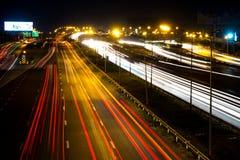 Darknight-Ampelspuren auf Straße Stockfotos