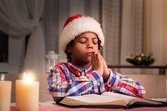 Darkskinned boy praying on Christmas. Royalty Free Stock Images