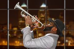 Darkskinned trumpeter in fedora hat. Royalty Free Stock Images