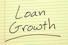 Darlehens-Wachstum auf einem gelben Kanzleibogenblock Stockbild
