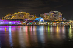 Darling Harbour nightscene. Colourful light reflections in the water at Darling Harbour. Darling Harbour in Sydney is a lively place with many bars and Stock Photo