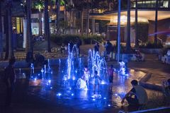 Darling Quarter Splash Pad. SYDNEY,NSW,AUSTRALIA-NOVEMBER 21,2016: Family playing by illuminated water splash pad feature at Tumbalong Park in Darling Quarter in Royalty Free Stock Images