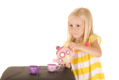 Darling young blond girl playing with a tea in striped shirt Royalty Free Stock Images