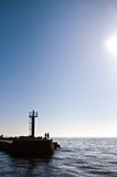 Darlowo port jetty beacon sunrise. A scenic landscape of Darlowo (Poland) jetty or pier with beacon with the sun and people silhouettes Stock Image