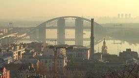 Darnystkyibriedgebrug met cityscape in Kiev, de Oekraïne tijdens nevelige ochtend met bezinning, 4k-lengtevideo stock videobeelden