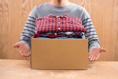 Darowizny pudełko dla biedy z odzieżą w męskich rękach Obraz Royalty Free