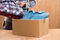 Darowizny pudełko dla biedy z odzieżą w męskich rękach Obrazy Royalty Free