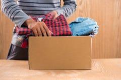 Darowizny pudełko dla biedy z odzieżą w męskich rękach Zdjęcia Royalty Free