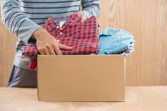Darowizny pudełko dla biedy z odzieżą w męskich rękach Obrazy Stock