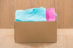 Darowizny pudełko dla biedy z odzieżą w męskich rękach Fotografia Stock