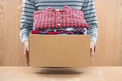 Darowizny pudełko dla biedy z odzieżą w męskich rękach Fotografia Royalty Free